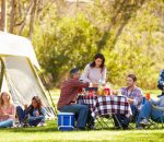 Two Families Enjoying Camping Holiday In Countryside
