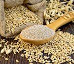 Bran flakes oat in spoon, a bag of grain oats, oat ears against the dark wooden board